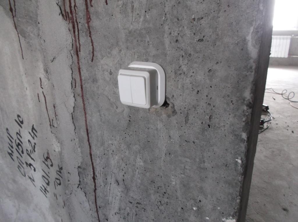 Накладной выключатель торчит из стены.